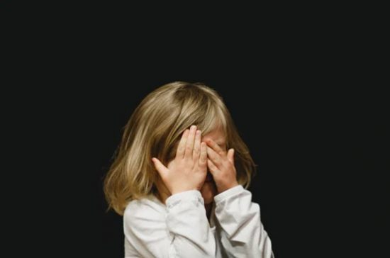 a child covers their eyes