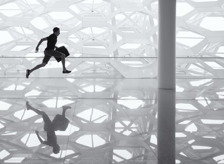 A man with a briefcase sprints inside a white room