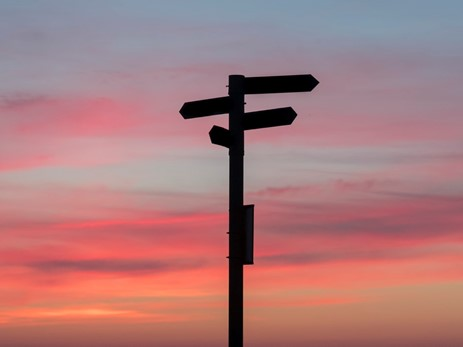 A sign post in front of a multi-coloured evening sky
