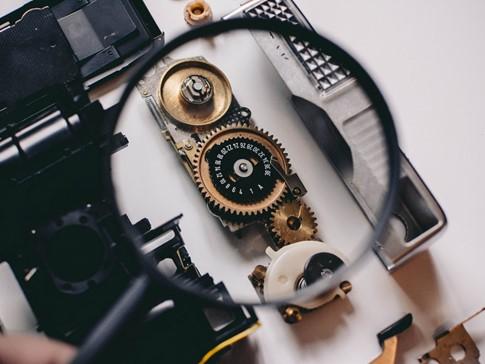 Eine Lupe wird über einem Uhrwerk gehalten