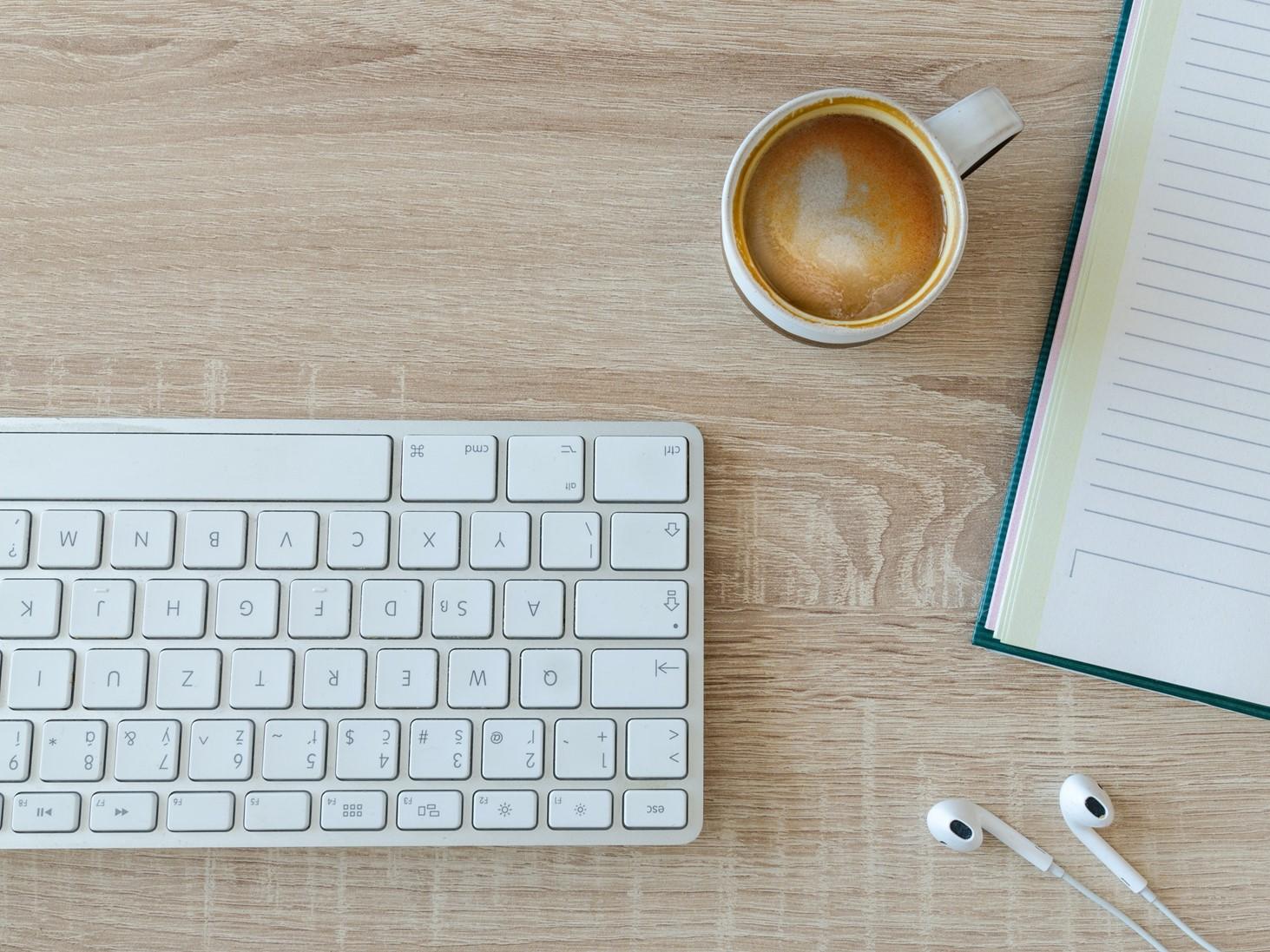 Bild von einer Tastatur, Kaffee, Kopfhörern und einem Notizbuch.