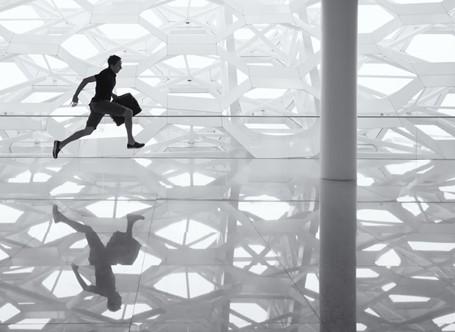 Ein Mann mit einer Brieftasche in der Hand sprintet in einem weißen Raum